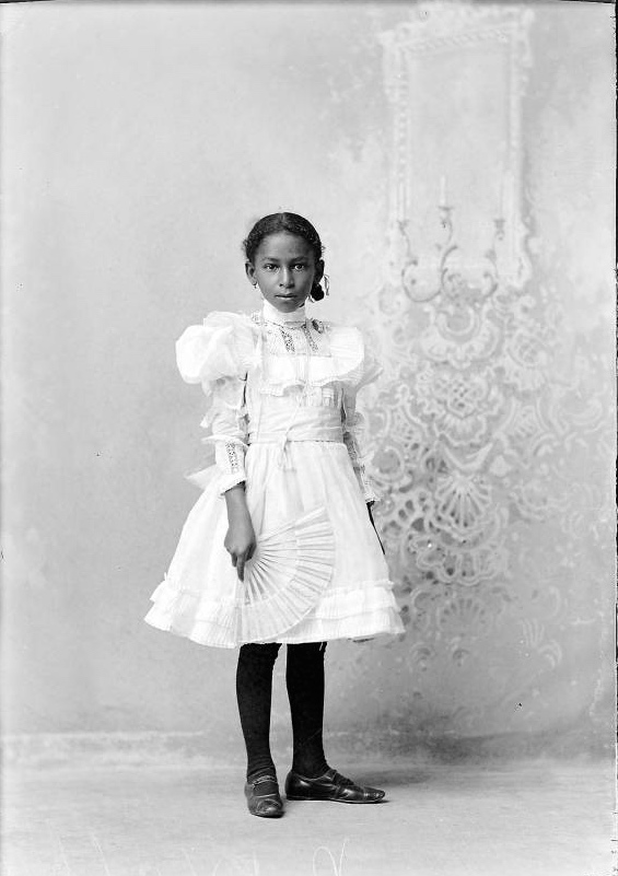 Studio portrait of African American young girl standing and holding a fan 2