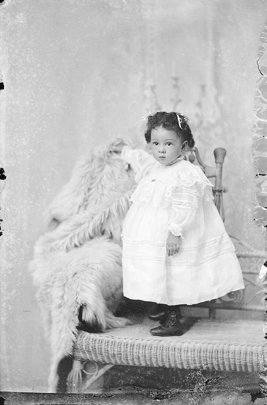 Studio portrait of young girl standing on a wicker couch 2